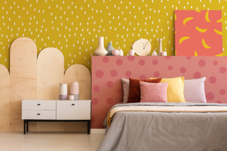 Colorful painting on grey bedhead of bed with cushions in bedroom interior with kavinet. Real photo